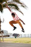 Skateboarder doing tricks and jumping on the road. Full body portrait of a cool skateboarder skating, doing tricks and jumping on the road Stock Image