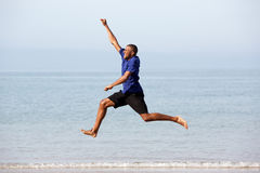 Portrait of excited young african guy running and jumping along the sea Royalty Free Stock Photo