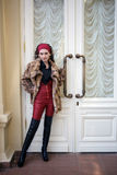 Full body portrait of fashion girl in front of the white door. Full body portrait of beautiful fashion young girl posing in front of the white door Royalty Free Stock Images