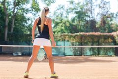 Full body portrait of female tennis player in action in a tennis court outdoor. View from back. Full body portrait of blonde female tennis player in action in a Royalty Free Stock Photo