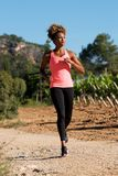 Full body fit young african woman running outdoors Royalty Free Stock Image
