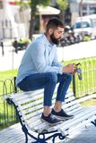 Full body handsome man sitting on bench with mobile phone Royalty Free Stock Photo