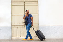 Full body handsome young guy walking with suitcase and talking on mobile phone. Full body portrait of a handsome young guy walking with suitcase and talking on Royalty Free Stock Photography