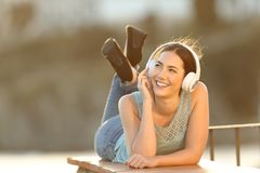 Happy girl listens to music looking at side royalty free stock photo