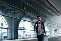 Full body portrait of a happy male traveler walking with bags and coffee Stock Photos