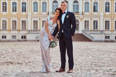 Portrait of happy newlyweds embracing against the backdrop of the facade of the beautiful old palace. royalty free stock photography