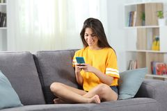 Happy teen in yellow using phone at home royalty free stock image