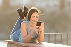 Happy woman using a smart phone lying in a balcony stock image