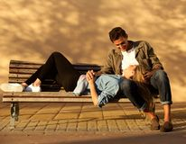 Full body happy woman and man in embrace on park bench stock image