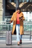 Full body happy young african american woman walking in station with suitcase and mobile phone stock photos