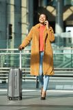 Full body happy young black woman walking in station with suitcase and mobile phone royalty free stock photo