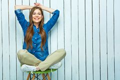 Full body portrait of hipster girl sitting on chair. Stock Images