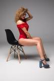 Full body portrait of a pretty smiling woman sits on chair on gr. Full body portrait of a pretty smiling woman sits on chair Royalty Free Stock Image