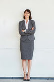 Full body portrait of professional business woman. Standing with arms crossed by white wall royalty free stock images