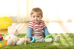 Full body portrait of a single kid sitting on the floor. Full body portrait of a single kid sitting on a carpet on the floor with toys at home stock photography