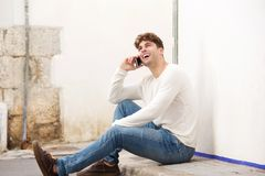 Smiling man sitting on sidewalk talking on mobile phone Stock Photos