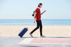 Full body portrait of smiling man walking by sea with suitcase and cellphone. Full body side portrait of smiling man walking by sea with suitcase and cellphone Royalty Free Stock Photography