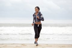 Full body sporty young black woman running on beach by water royalty free stock photos