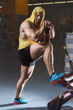 Full body portrait of tired sporty male after workouts on power exercise machine in a gym club. Stock Image