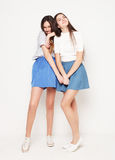 Full body portrait of two happy  girls over white background. Full body portrait of two happy  girls wearing blue skirts over white background Stock Images