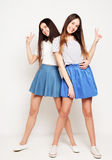 Full body portrait of two happy  girls over white background. Full body portrait of two happy  girls wearing blue skirts over white background Royalty Free Stock Images