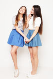 Full body portrait of two happy  girls over white background. Full body portrait of two happy  girls wearing blue skirts over white background Royalty Free Stock Photos