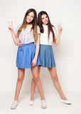 Full body portrait of two happy  girls over white background. Full body portrait of two happy  girls wearing blue skirts over white background Stock Photo