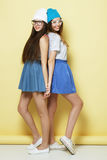 Full body portrait of two  hipster girls over yellow background Royalty Free Stock Images