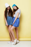 Full body portrait of two  hipster girls over yellow background Royalty Free Stock Image