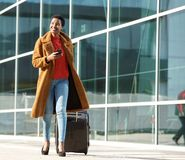 Full body young black woman walking outdoors with luggage and mobile phone stock images