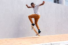 Full body young male skateboarder doing a trick outdoors Stock Photos