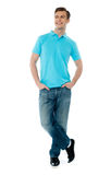 Full-body pose of smiling man. Posing in casuals with crossed legs Royalty Free Stock Image