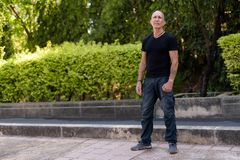 Full body shot of bald senior tourist man standing while thinkin. G at peaceful park in Bangkok Thailand stock photos