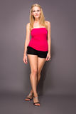 Full body shot of female model. In hot pants and pink tank top Royalty Free Stock Images
