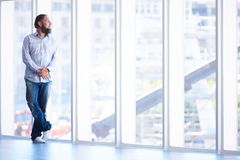 Full body shot of man with beard looking out window Royalty Free Stock Photography