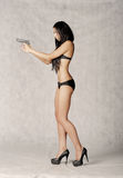Full body shot of a sexy brunette with gun in her hands Stock Images