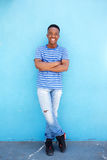 Full body smiling young african man leaning against blue background Stock Photos