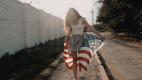 Full body smiling young American girl with American stars and stripes flag weaving in the wind, retro color stock video footage