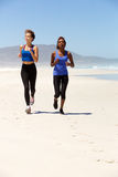 Full body two healthy women running on the beach Stock Photos