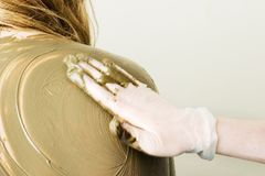 Full Body Wrap. A sea mud full body wrap at a luxury spa being applied to the back and shoulders with motion blur on the hand applying the mud Royalty Free Stock Photo