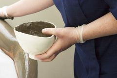 Full Body Wrap Detail. A detail image of a sea mud full body wrap at a luxury spa being applied to the arm Stock Images