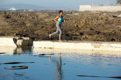 Full body young black woman running by water Royalty Free Stock Photos