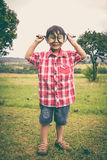 Full body. Young boy exploring nature with magnifying glass. Out Stock Image