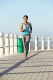 Full body young fitness woman running on promenade Royalty Free Stock Images