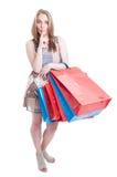 Full body of young stylish shopaholic with shopping bags shushing Royalty Free Stock Photo