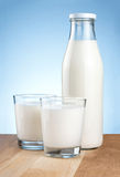 Bottle of fresh milk and two glass is wooden table Stock Photos