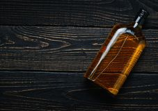 Bottle of whiskey on a  black wooden table.Top view. Stock Photography