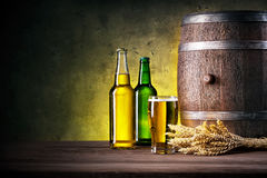 Full bottles of beer and glass with barrel Stock Image