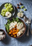 Full bowl with baked sweet potatoes, barley, arugula and apples. Vegetarian buddha bowl with autumn vegetables and grains, on a bl royalty free stock photo
