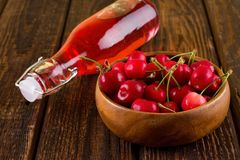 Full bowl with cherries in front of bottle with red drink Stock Image